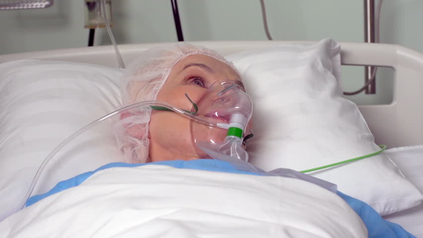 Close-up of an elderly woman with an oxygen mask lying in bed before surgery