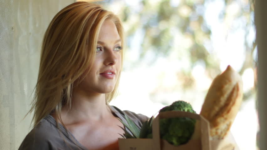Attractive young blonde woman waits and then delivers groceries to a home.  No