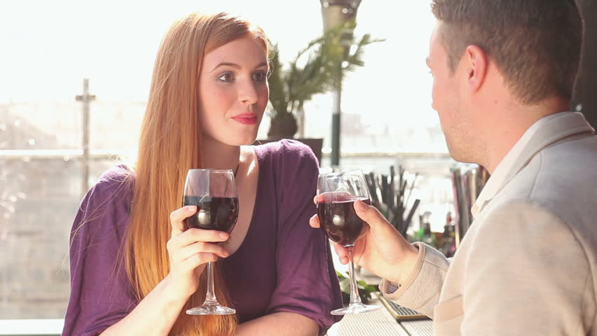 Loving couple talking while having glass of red wine on a terrace