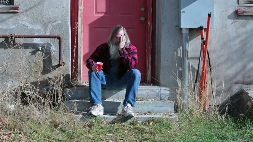 Sad poor homeless man long hair and beard HD. Red plaid jacket and red  cup for drink and drinking.  Homeless man down on luck, poor, hungry and depressed sits on steps of abandoned building.