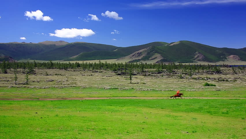 Man riding horse in Mongolian landscape, near Terkhiin Tsagaan Lake, Central Mongolia