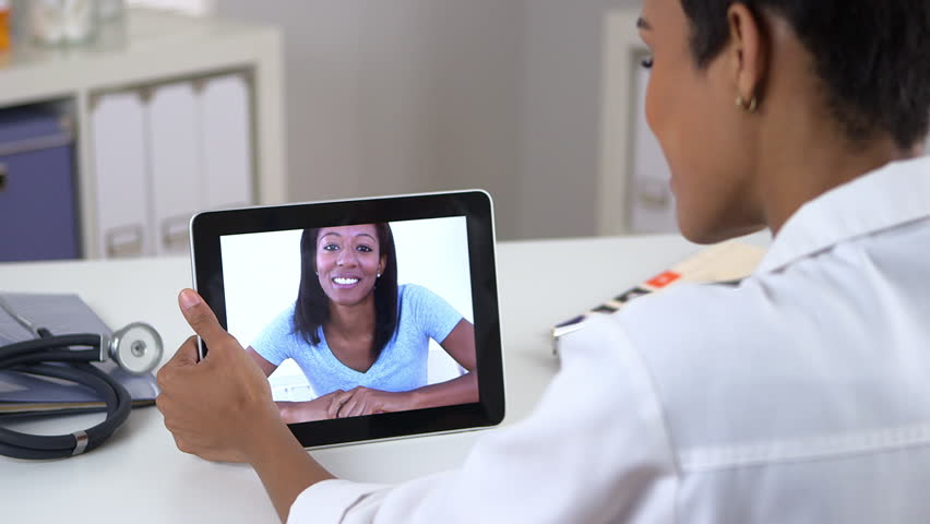 African American woman video chatting with doctor on ipad