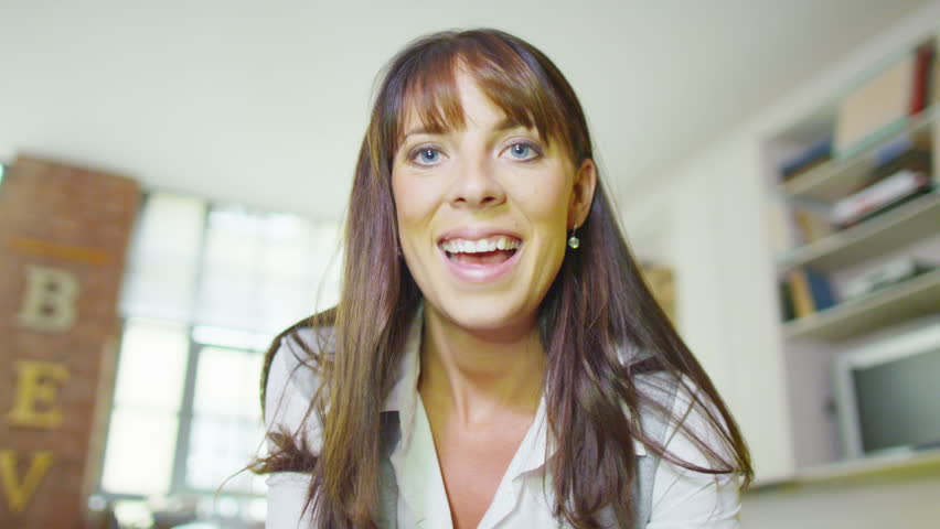 Happy attractive young woman having a video chat, as seen from the point of view of the computer screen.