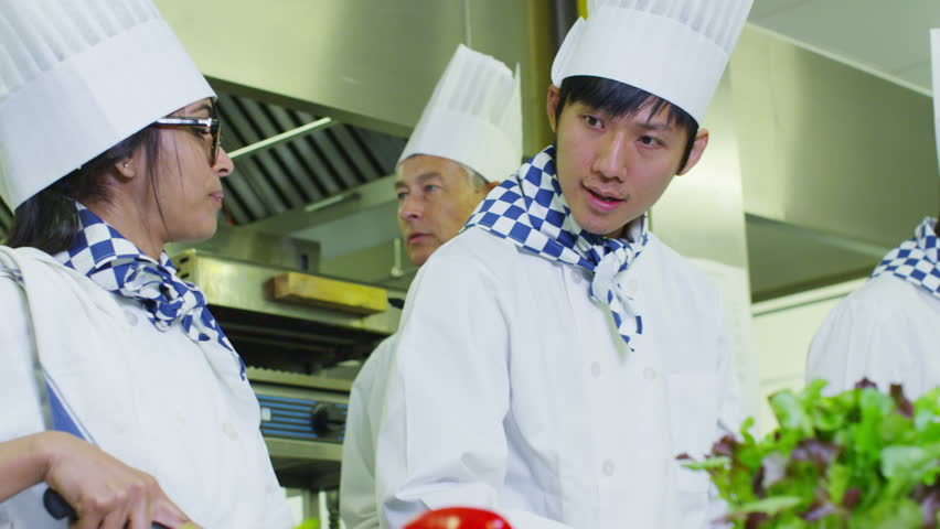 Mixed ethnicity team of professional chefs preparing food in a commercial kitchen.