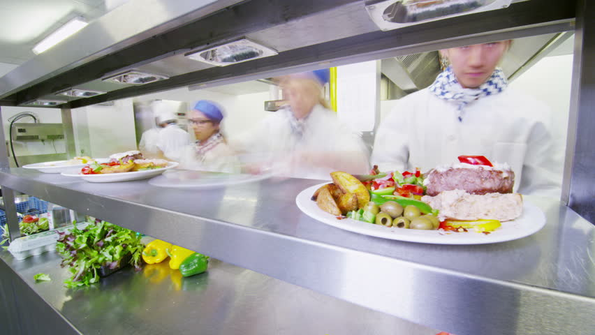 Time lapse of a busy team of chefs preparing and serving food in a commercial kitchen.