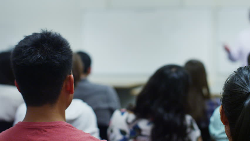 View from behind of a large mixed ethnicity group of students in a classroom, listening as their teacher holds a lecture. One student puts up his hand to ask a question.
