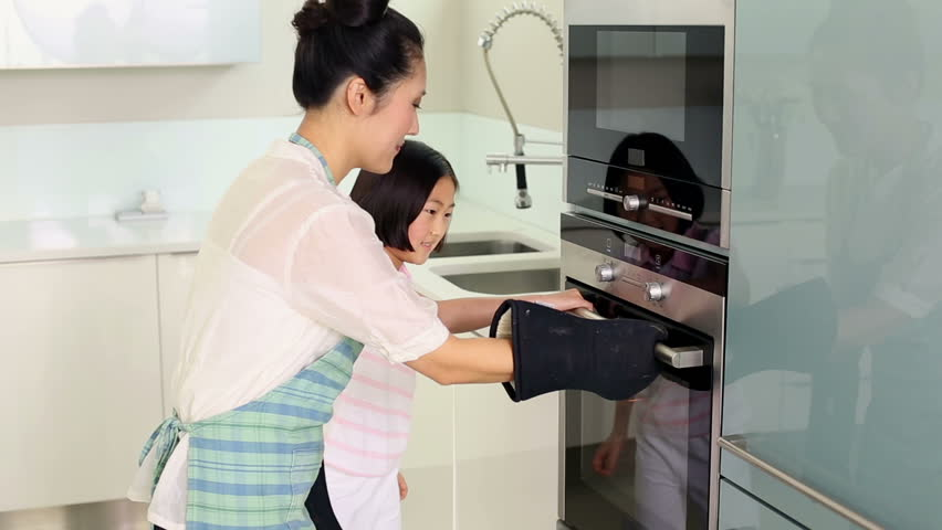 Mother taking baking tray out of oven in bright kitchen