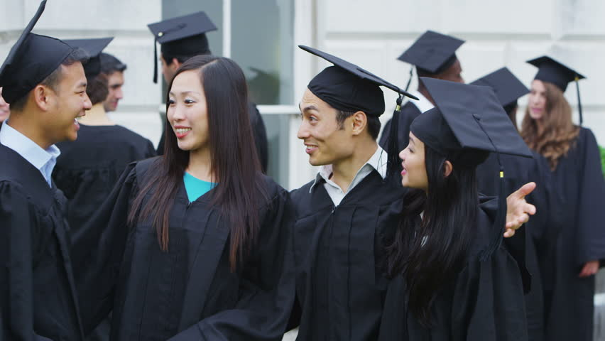 Portrait of a happy asian group of student friends standing together outdoors on graduation day.