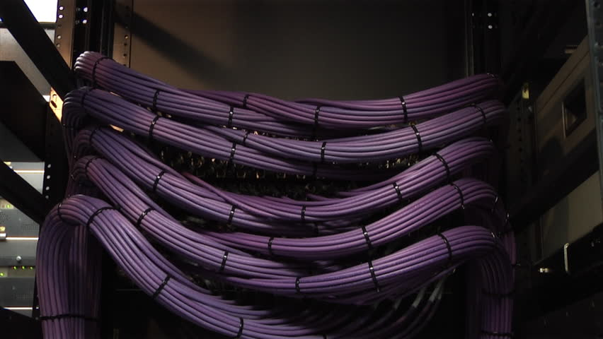 This high definition footage is of a video server cables.  The camera pans slowly down to reveal a organized video cable structure
