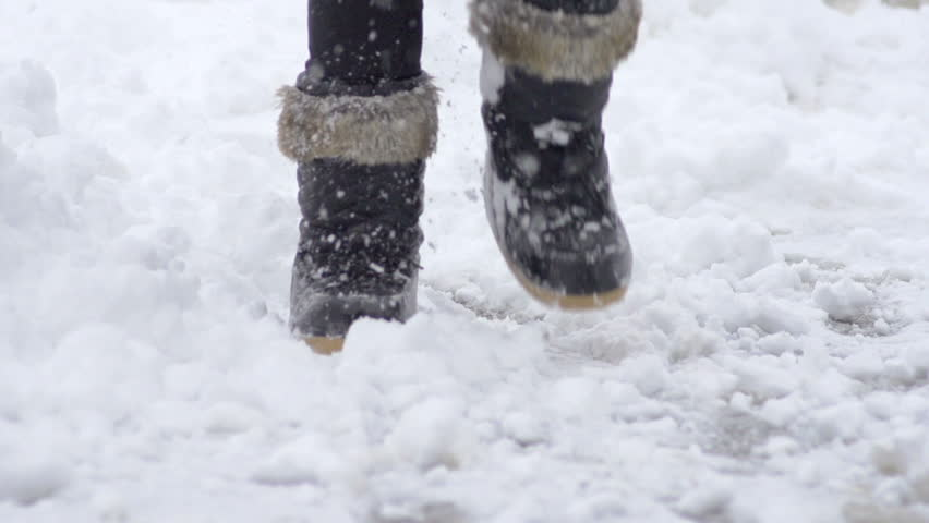 Slow Motion Of Female Legs Wearing Black Snow Boots Walking Though Fresh Snow On