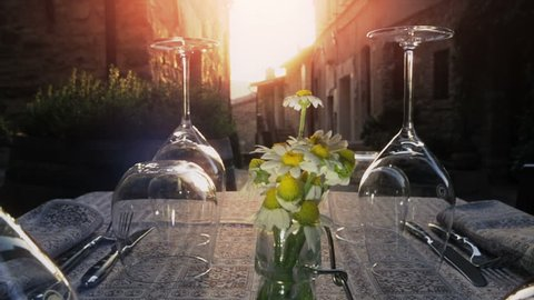 Table with wine glasses of wedding arrangement when sunset falls over ancient borgo
