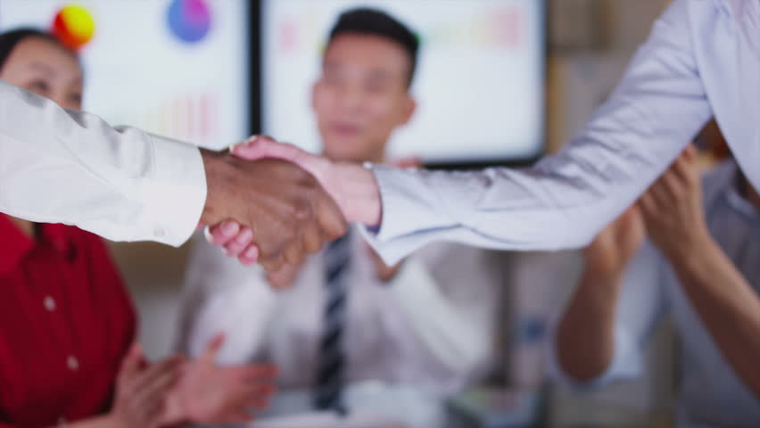 Financial business group negotiating a deal in the boardroom. When the calculations are favorable, hands reach across the table to shake hands on the deal.