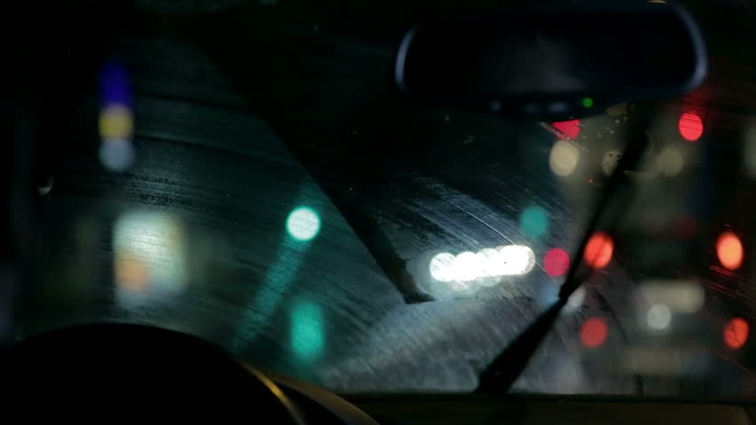 Car wipers remove rain gathered on windscreen on night ride through city