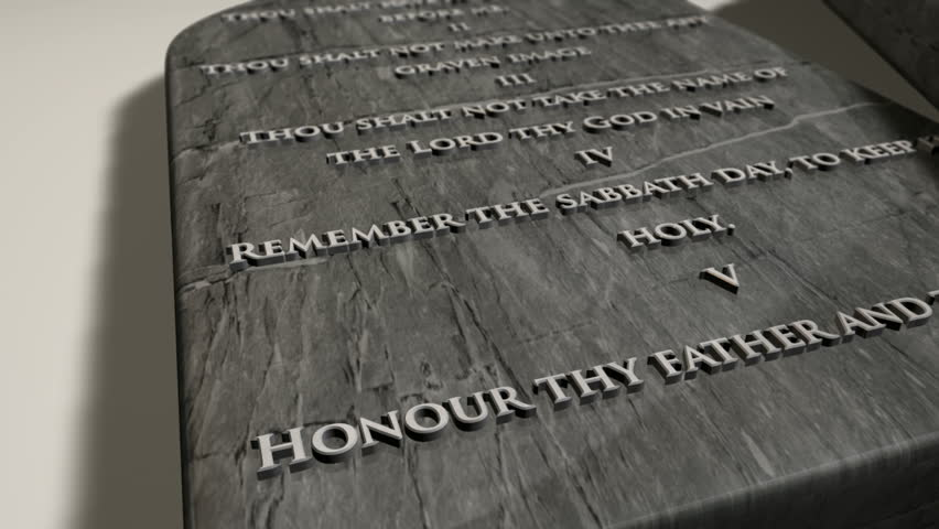 A slow close up pan across two stone tablets with the ten commandments inscribed onto them on an isolated background