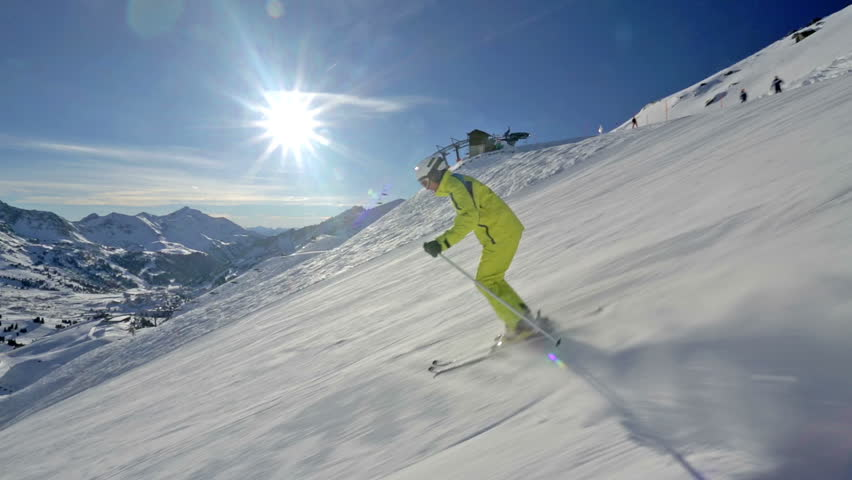 Side view alpine skier skiing short swings on ski slope on sunny winter day in Austrian mountains | Shutterstock HD Video #5196587