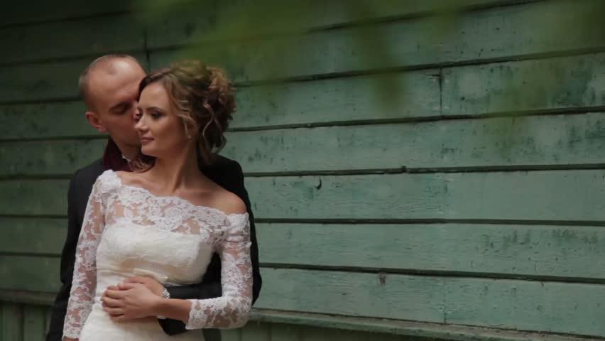 Beautiful wedding couple near a blue wall