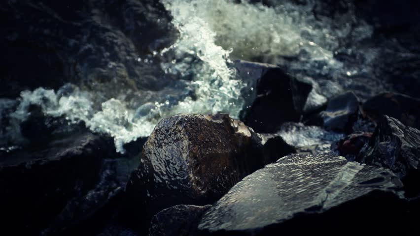 Water splashing against rocks (super slow motion)