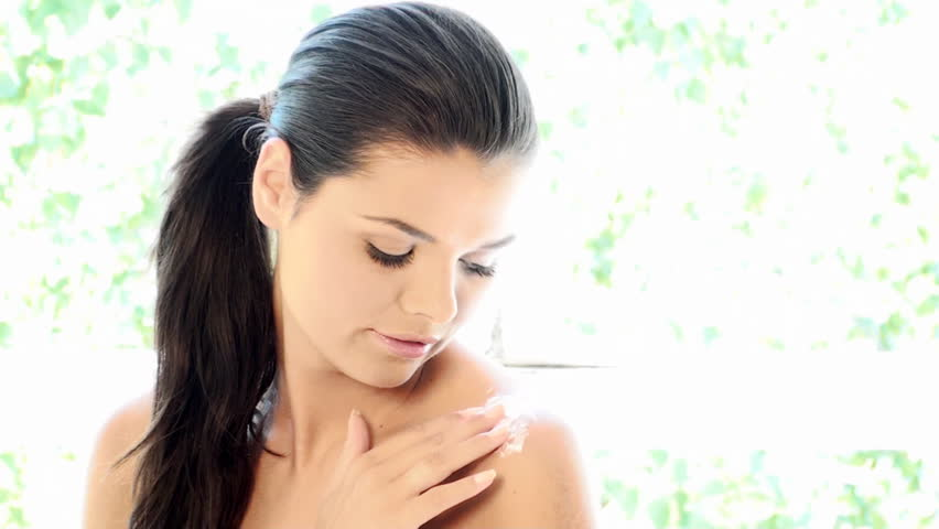Portrait of beautiful and relaxed lady is applying cream