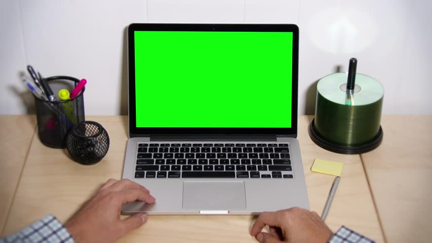 A man taps his fingers on his desk waiting for his laptop to operate. Green