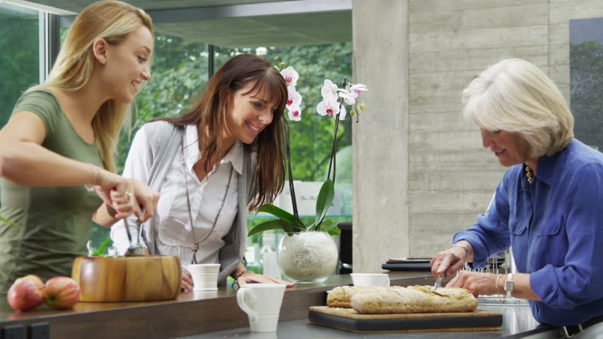 Happy female friends or family members preparing a meal with freshly baked bread in modern kitchen.   Shutterstock HD Video #5234435