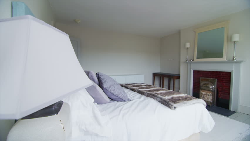 View of elegant bedroom and en suite bathroom in a stylish, classically designed home with a contemporary feel. No people.
