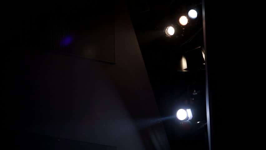 Floodlights in the theatre. Lamp man operating with cool light device.