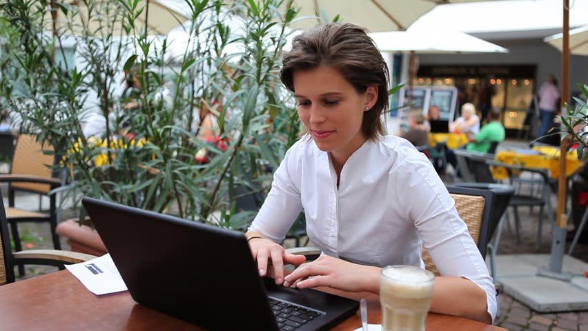 Young businesswoman with laptop in outdoor cafe