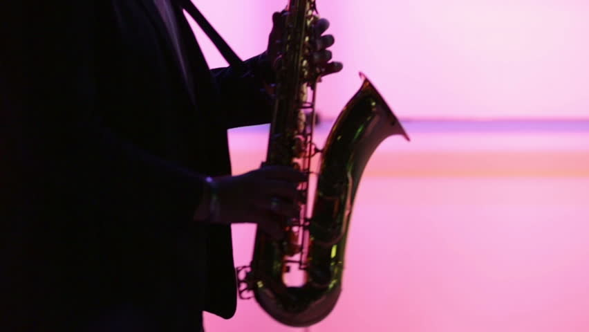 Man playing sax while making smooth dance moves silhouetted