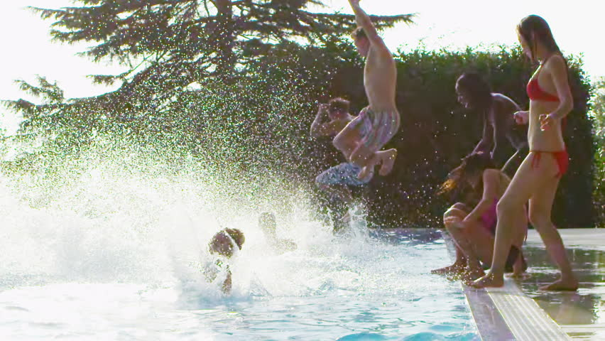 Happy fun loving group of friends jumping, splashing and playing in the swimming pool at a pool party. In slow motion.