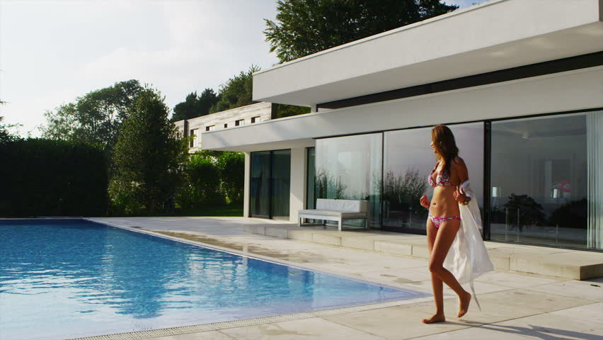 Beautiful woman outside contemporary home slips out of her robe and steps down into the pool to take a swim. In slow motion.
