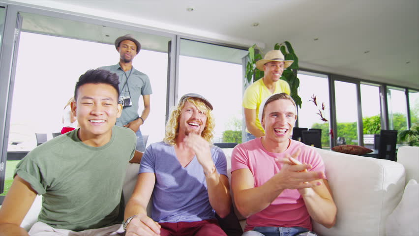 Happy group of male friends watching sports on TV and cheering on their team.