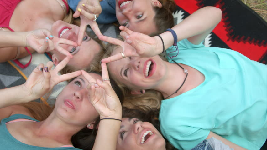Group Of Five Animated Teenage Girls Lying On Their Backs, Heads Together, Forming A Star With Their Fingers, Shot From Above