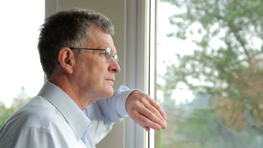 Close up, middle aged man looks out of the window, smiles and waves at someone