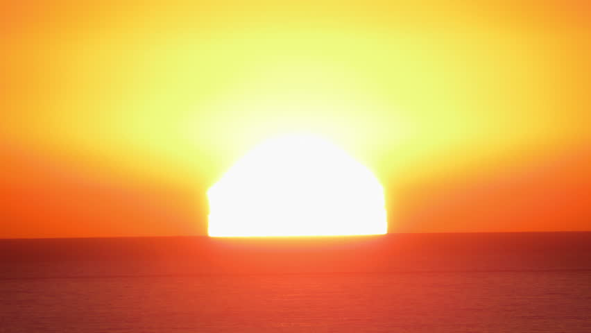 A time lapse of the large orange sunset as the massive sun sets into the horizon above the ocean  | Shutterstock HD Video #5307365