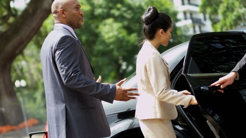 Close up successful male female business advisers getting into luxury black limousine after arriving for important meeting shot on RED EPIC, 4K, UHD, Ultra HD resolution