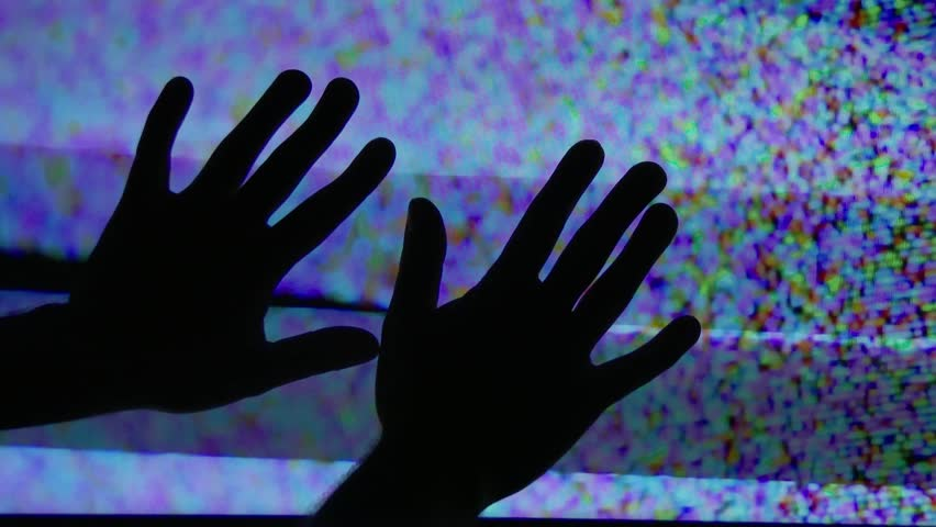 A mysterious set of hands touch the static on a television screen.
