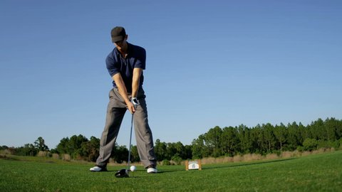 Caucasian male golf professional using driver to tee off on fairway at luxury golf resort shot on RED EPIC, 4K, UHD, Ultra HD resolution