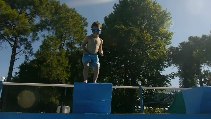 Boy jumping and diving in Swimming Pool -Slow Motion- Perfect for videos about: swimming, pools, summer fun, vacation, getaways, underwater footage, kids, beating the heat, and exercise.