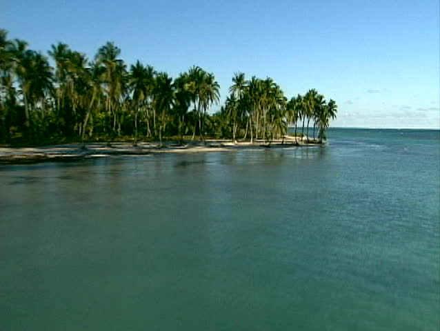 aerial trucking video of deserted island in the Caribbean with pristine beaches and palm trees