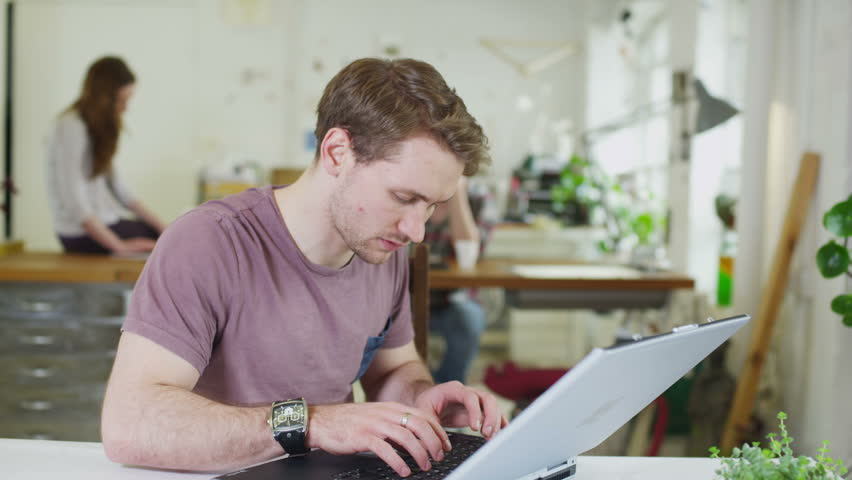 Young male student concentrating as he works within a shared study space | Shutterstock HD Video #5395673
