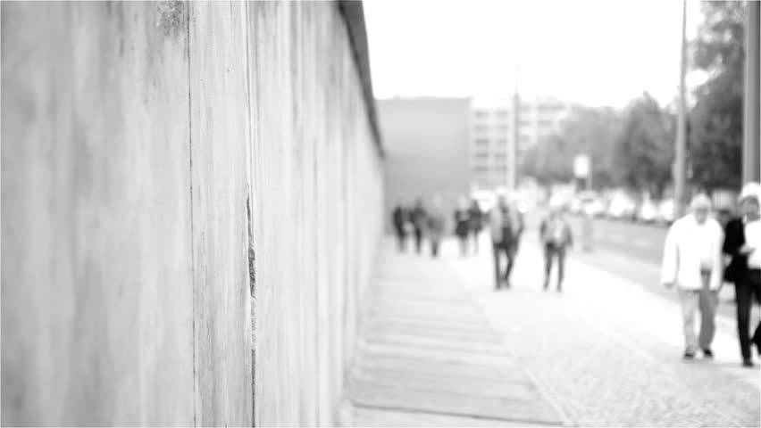BERLIN, GERMANY - OCTOBER 8, 2013: Close-up of Berlin Wall, tourists walk past. grayscale.