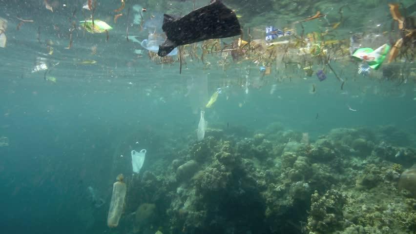 Plastic garbage and other debris floating underwater over fragile coral reef in Bunaken Island, Sulawesi