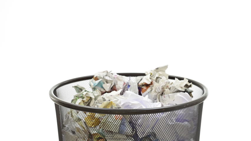 Throwing paper into the waste basket: Bin filled by useless documents