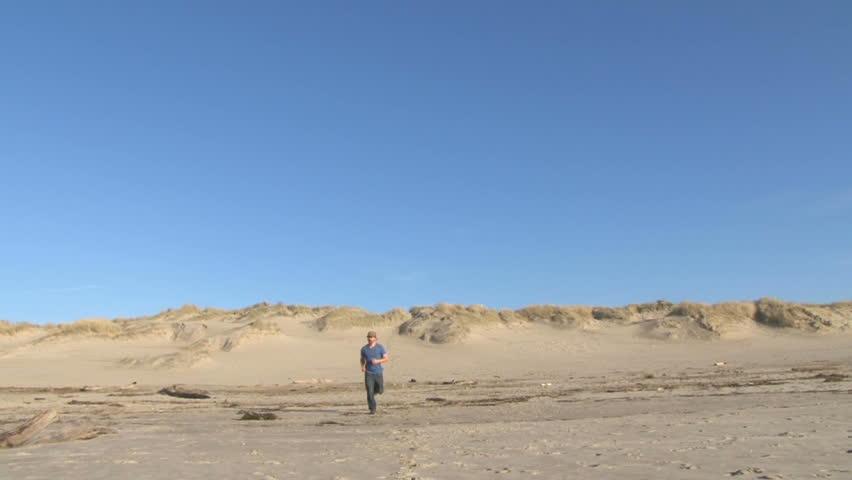 Man running down sand dune on blue sky day.