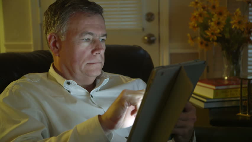 Relaxing at home using his tablet pc a mature handsome man smiles contentedly.   Shutterstock HD Video #5483882