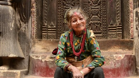 Nepal. Kathmandu. Happy woman sits near the entrance of the temple