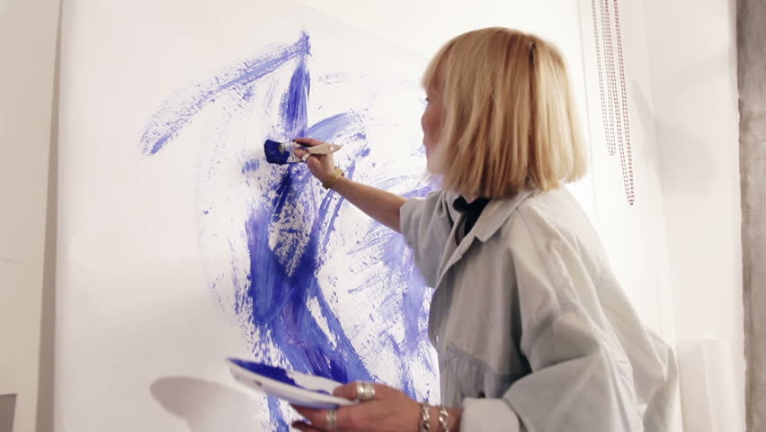 Woman artist painting with paintbrush