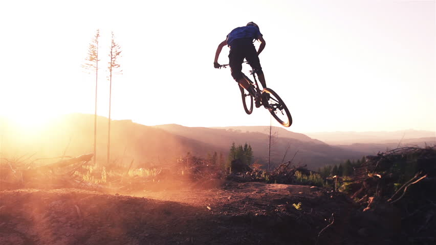 Mountain biker jumping at sunset in super slow motion