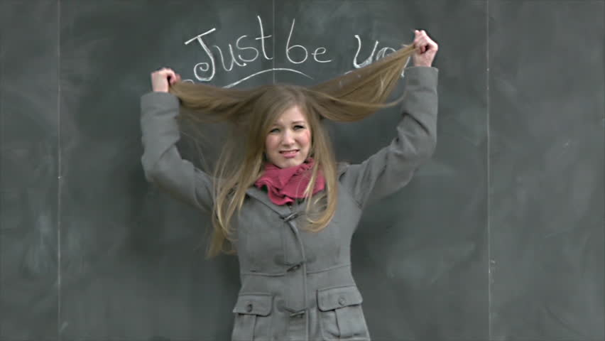 "Cute Girl Holds Out Her Hair Under A Chalkboard ""Just Be You"" Sign"