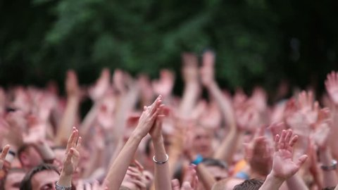 MOSCOW, RUSSIA - JUNE 23, 2012: People raise their hands up and applaud at a concert of Chaif rock-band during VII traditional festival of live sound Music of Summer in Hermitage Garden